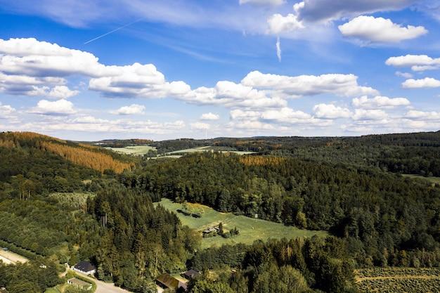 Foto aérea de uma paisagem montanhosa coberta de árvores