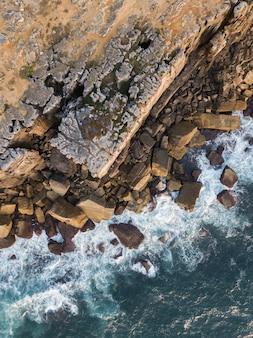 Foto aérea de uma parede acidentada em ruínas com pedaços de rocha caídos em uma costa ondulada em peniche, portugal