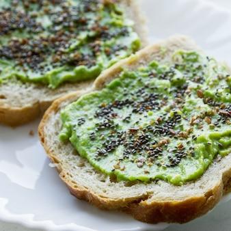 Foto aérea de uma pasta de pão com creme de abacate com sementes de chia