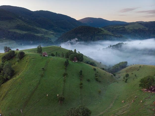 Foto aérea de uma pequena casa em uma incrível paisagem montanhosa na transilvânia, romênia