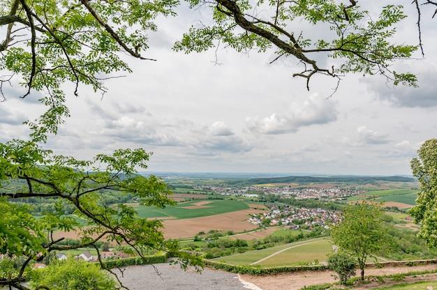 Foto aérea de uma pequena cidade cercada por uma natureza incrível em primeiro plano de galhos de árvores