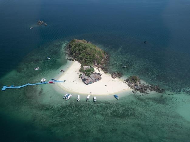 Foto aérea de uma pequena ilha com alguns prédios e barcos e um cais azul