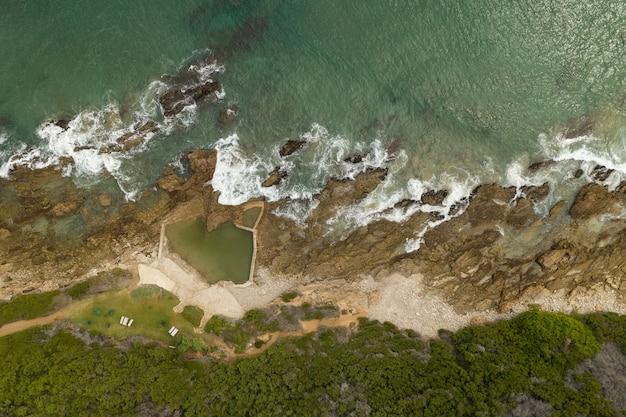 Foto aérea de uma praia com água verde pura durante o dia