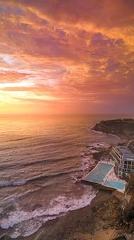 Foto aérea de uma praia com uma grande piscina de um hotel e o mar durante o pôr do sol