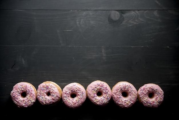 Foto aérea de uma superfície de madeira preta com rosquinhas rosa no fundo grande