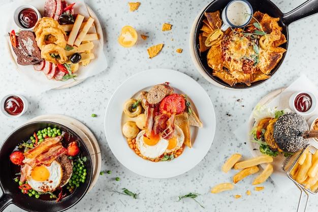 Foto aérea de uma variedade de fast food, carnes e lanches