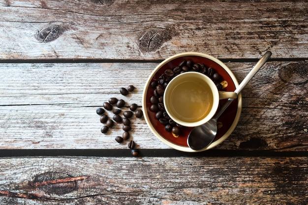 Foto aérea de uma xícara de café perto de grãos de café e uma colher de metal numa superfície de madeira