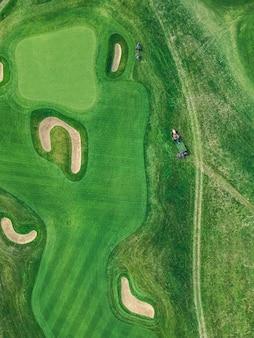 Foto aérea do clube de golfe, gramados verdes, árvores, estrada, cortadores de grama, flat leigos
