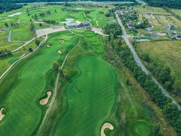 Foto aérea do clube de golfe, gramados verdes, árvores, estrada, cortadores de grama,