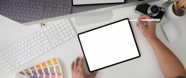 Foto aérea do designer trabalhando em tablet com câmera computador dispositivo e designer suprimentos