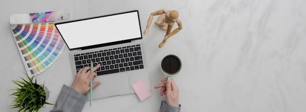 Foto aérea do designer trabalhando no laptop mock-up e bebendo café