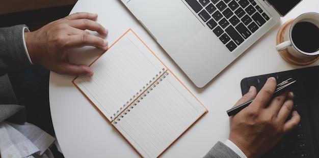 Foto aérea do empresário profissional, planejando seu projeto, escrevendo sua idéia no caderno em branco