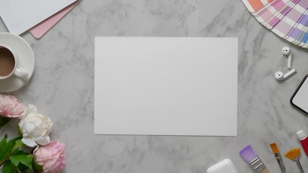 Foto aérea do espaço de trabalho de design com papel de desenho, ferramentas de pintura e xícara de chá na mesa de mármore