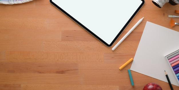 Foto aérea do estúdio confortável artista com ferramentas de pintura e material de escritório na mesa de madeira