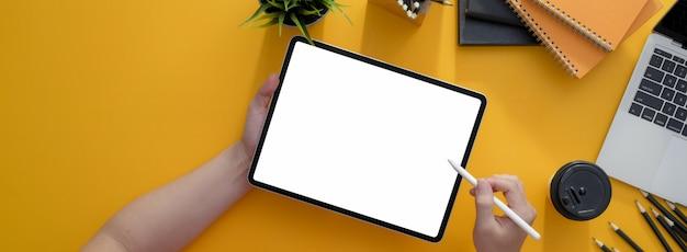 Foto aérea do freelancer, escrevendo no tablet de tela em branco com caneta na mesa de trabalho amarela