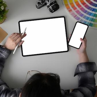 Foto aérea do freelancer feminino trabalhando em seu projeto com tablet, smartphone e designer de suprimentos