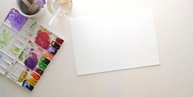 Foto aérea do local de trabalho do artista moderno com papel de desenho e ferramentas de pintura na mesa branca