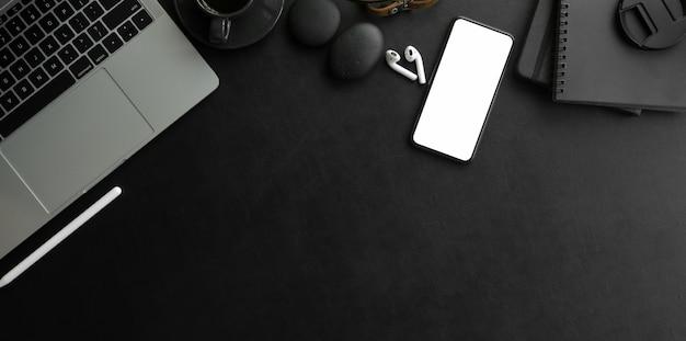 Foto aérea do local de trabalho moderno escuro com computador portátil e material de escritório