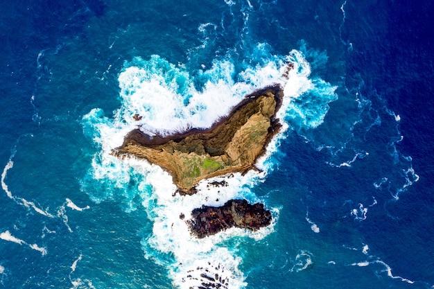 Foto aérea do mar azul e uma pequena ilha