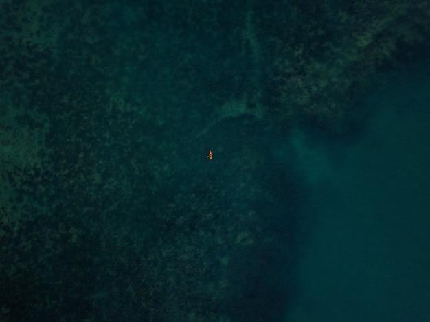 Foto aérea do mar com um pequeno caiaque visível à distância