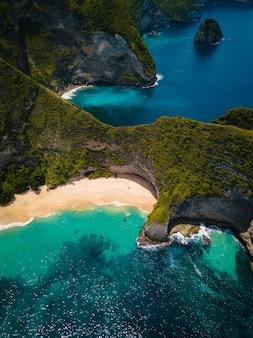 Foto aérea do oceano cercado por belas falésias cobertas de verde