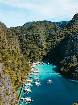 Foto aérea do oceano cercado por belas montanhas cobertas de verdes