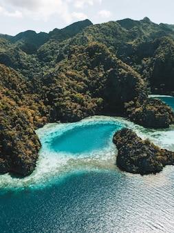 Foto aérea do oceano cercado por montanhas cobertas de verdes