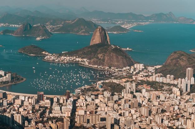 Foto aérea do rio de janeiro cercado pelo mar e morros sob o sol no brasil