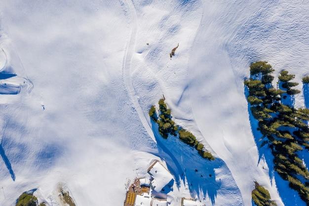 Foto aérea dos penhascos cobertos de neve capturada em um dia ensolarado