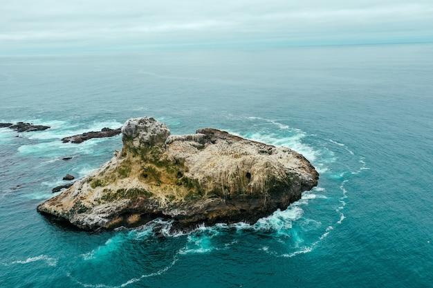 Foto aérea drone de uma pequena ilha rochosa no oceano azul lindo