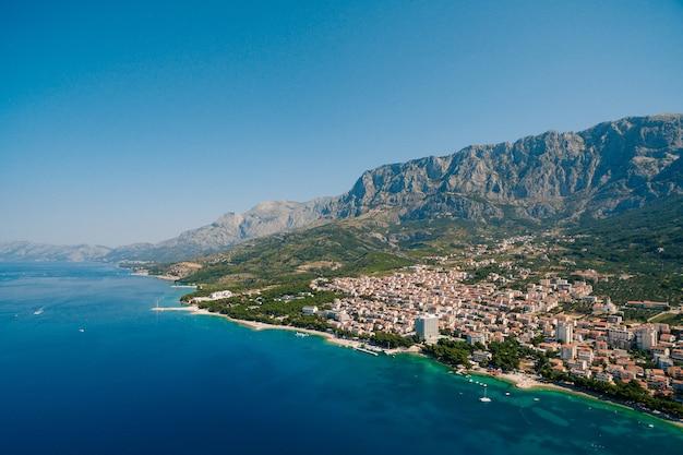 Foto aérea drone makarska, croácia. cidade costeira, mar e montanhas