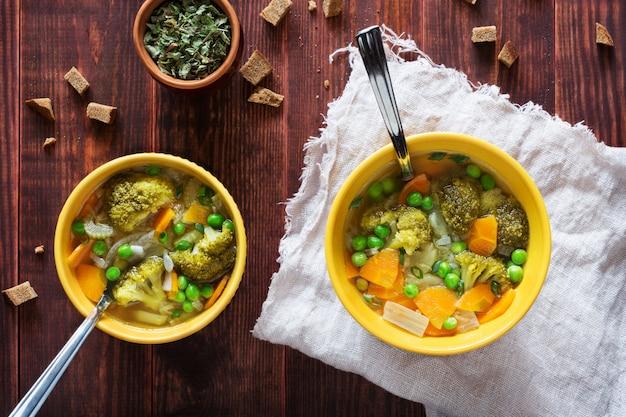 Foto aérea horizontal de sopa de legumes com cenoura, ervilhas e brócolis