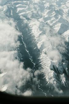 Foto aérea vertical das montanhas cobertas de neve