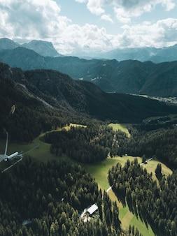 Foto aérea vertical de montanhas sob um céu azul e nuvens brancas