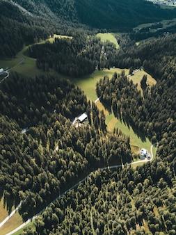 Foto aérea vertical de montanhas verdes com nuvens brancas ao fundo
