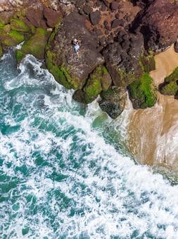 Foto aérea vertical de uma mulher com vestido azul deitada na praia rochosa