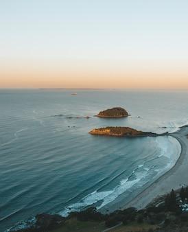 Foto aérea vertical de uma praia com pedras e um céu claro