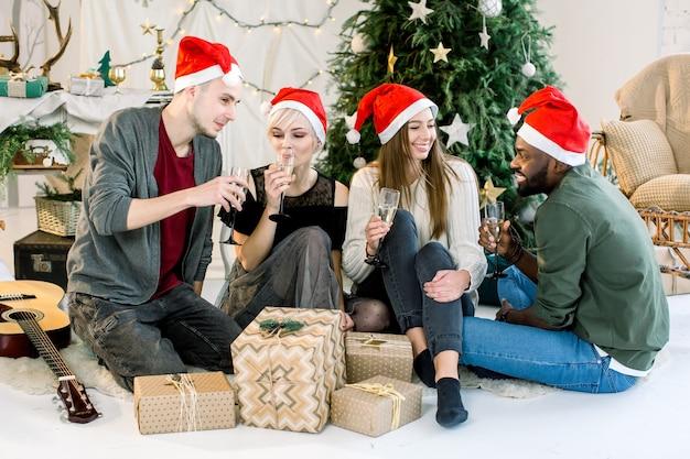 Foto alegre de quatro amigos comemorando o ano novo com champanhe em um quarto aconchegante e decorado