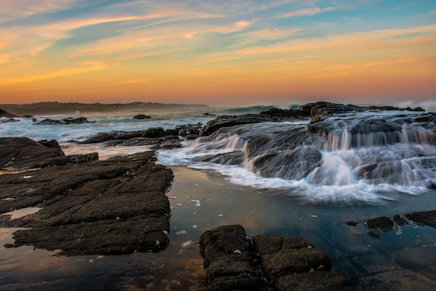 Foto ampla da praia com formações rochosas durante o pôr do sol com um lindo céu