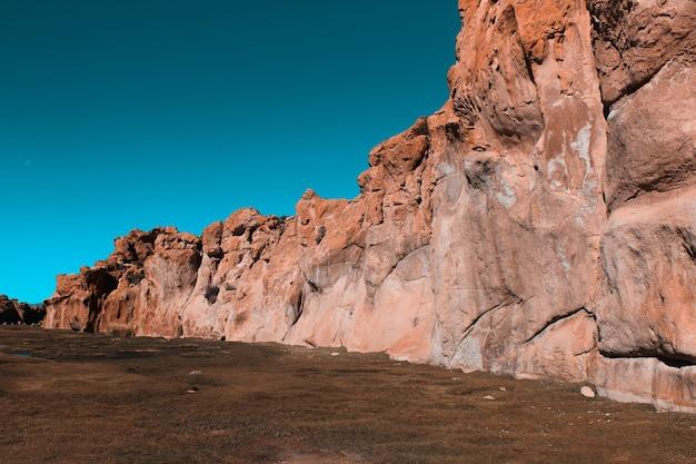 Foto ampla de penhascos cercados por terra com céu azul em um dia ensolarado
