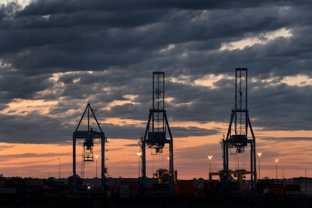 Foto ampla de três torres em um porto durante o pôr do sol em um dia nublado