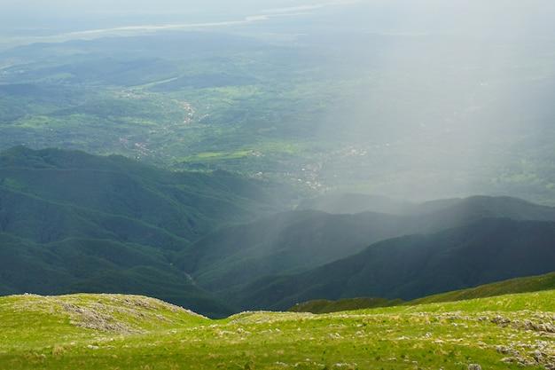 Foto ampla de uma bela cordilheira com céu nublado e nevoeiro