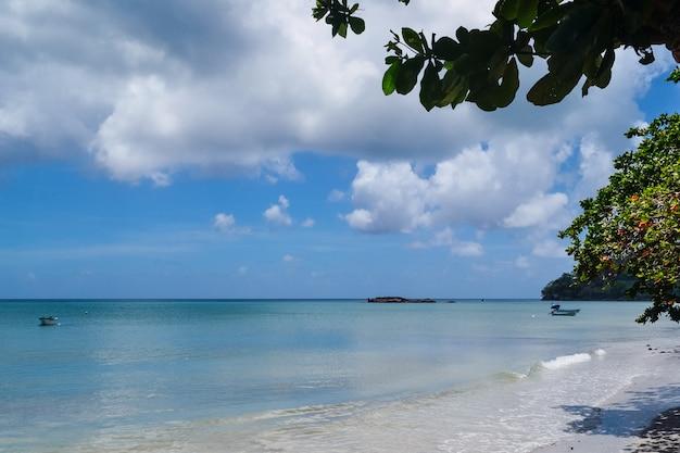 Foto ampla de uma bela praia de areia com um céu azul nublado ao fundo