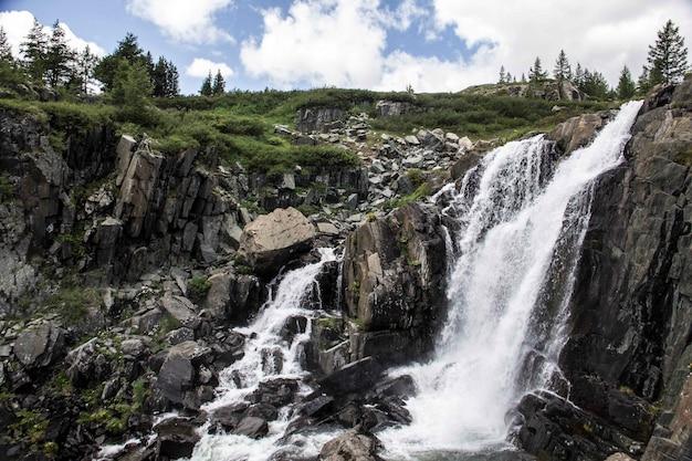 Foto ampla de uma cachoeira em um penhasco com grama e árvores na superfície em um dia nublado
