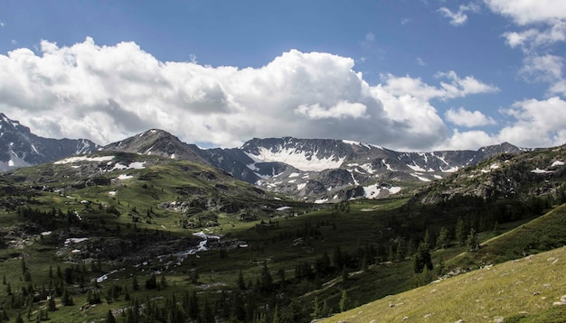 Foto ampla de uma cadeia de montanhas com árvores ao redor e uma espessa camada de nuvens no céu