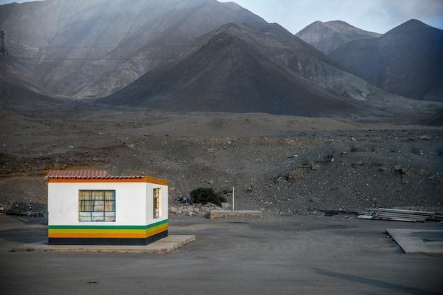Foto ampla de uma casa no meio de um campo com montanhas em um dia sombrio