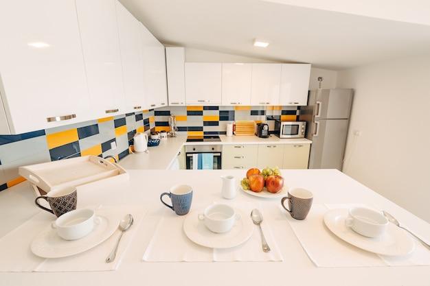 Foto ampla de uma cozinha em estilo branco com mesa, xícaras e frutas para três pessoas