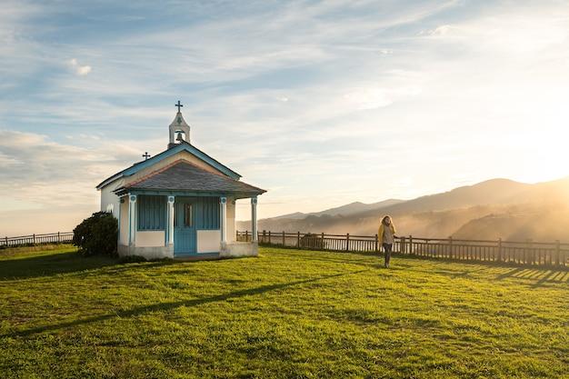 Foto ampla de uma mulher caminhando ao lado de uma pequena capela em um penhasco durante o nascer do sol