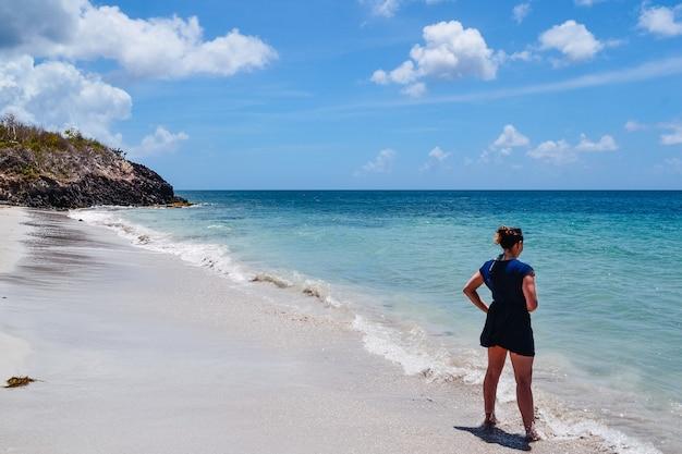 Foto ampla de uma mulher em pé na praia apreciando a vista do oceano