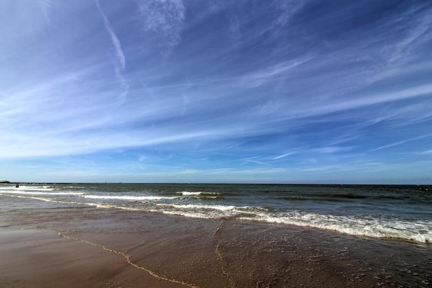 Foto ampla de uma praia de areia com céu azul claro